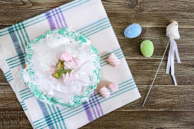 Pasen cake - kulich met gedroogde vruchten, versierd met meringue op een houten tafel.