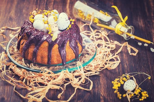 Pasen-cake met chocolade met gekleurde kwartelseieren die wordt verfraaid