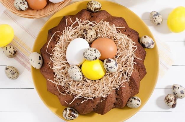 Pasen-cake met geverfte eieren in een nest, gele narcissen in een kop op een witte rustieke houten achtergrond
