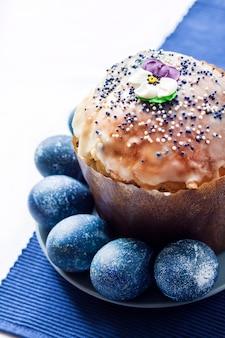 Pasen-cake met suikerbloem en blauw gekleurde eieren op een plaat op witte en blauwe doek wordt verfraaid die