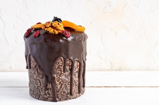 Pasen cake of kulitch met geglazuurd met chocolade en versierd met noten, gedroogde bessen en fruit op witte houten tafel.