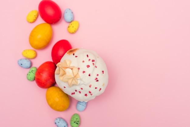 Pasen-cake op een roze achtergrond naast gekleurde kwartelpastelkleur en kippeneieren. paaskaart