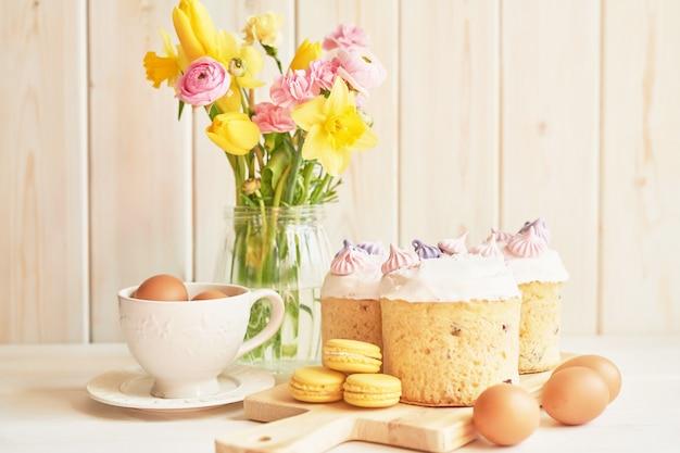 Pasen-cakes op lijst, makarons, eieren en boeket van bloemen in vaseaster