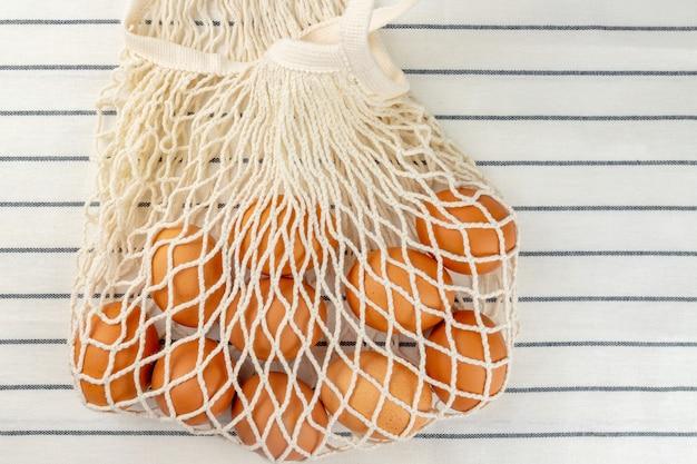 Pasen concept. geen plastic zakconcept. minimalistische stijl. beige mesh boodschappentas met bruine kippeneieren op textiel achtergrond.