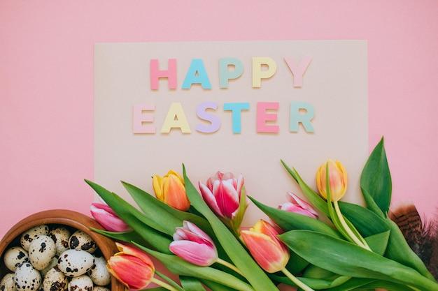 Pasen-concept. het gelukkige pasen-document sneed inschrijving met roze en rode tulpen en kwartelseieren op roze achtergrond. ruimte kopiëren, plat leggen.