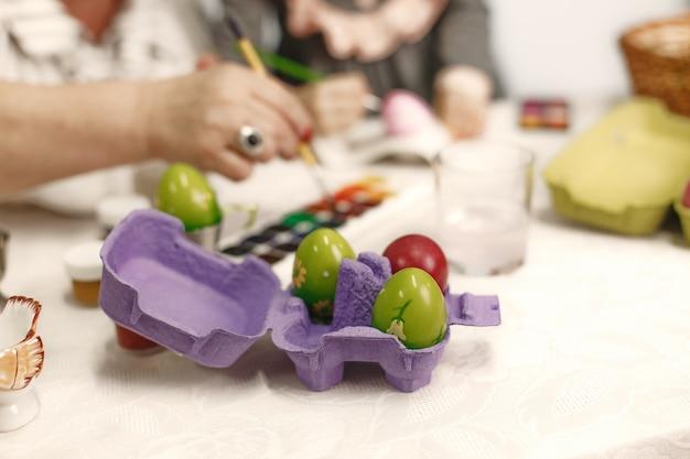 Pasen concept. klein meisje en haar grootmoeder die eieren voor pasen kleuren. close-up foto.