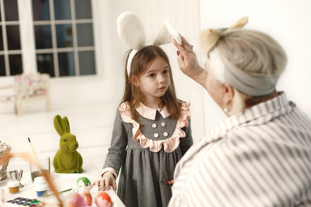 Pasen concept. klein meisje en haar grootmoeder die eieren voor pasen kleuren.