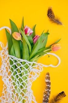 Pasen-concept. lente boeket van veelkleurige tulpen in eco tas met en kwarteleitjes en veren op een gele achtergrond. ruimte kopiëren, plat leggen achtergrond.