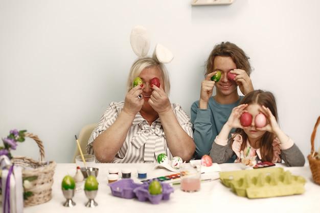 Pasen concept. meisje met broer en grootmoeder die eieren voor pasen kleuren.