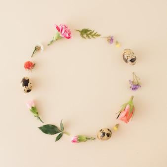 Pasen-concept, met eieren en kleurrijke lentebloemen, rozen, groene bladeren, gerangschikt in een cirkel met kopieerruimte op een pastelachtergrond. plat liggen.