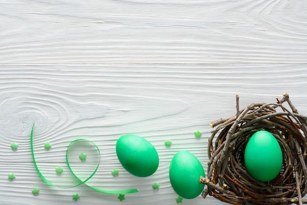 Pasen-concept met groene eieren in het nest op houten lijst.