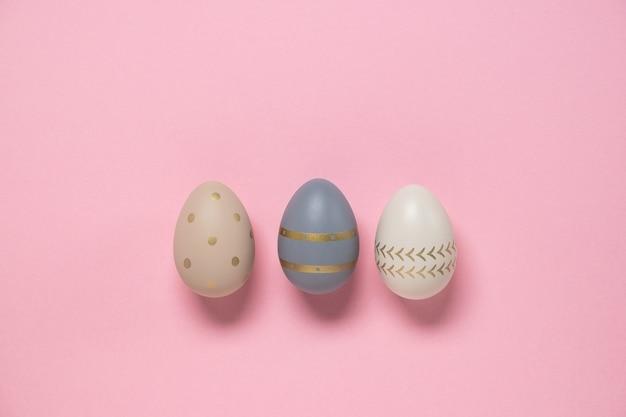 Pasen concept. versierde eieren staan op een rij op roze achtergrond.