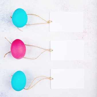 Pasen concept. witte lege label tags op roze en blauw gekleurde eieren bovenaanzicht plat leggen