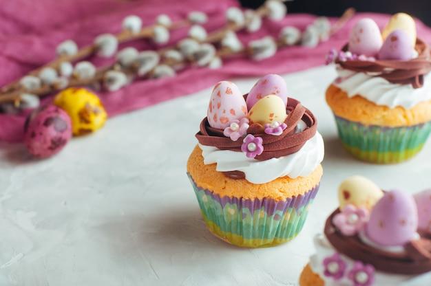 Pasen-cupcakes met suikergoedeieren wordt verfraaid in nest dat
