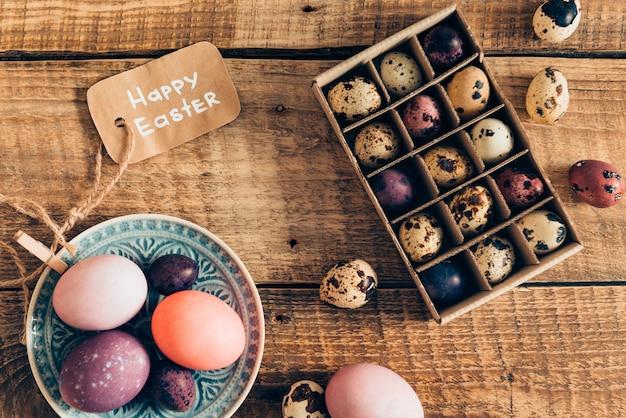 Pasen decor. bovenaanzicht van gekleurde paaseieren op plaat en paaskwarteleitjes in doos liggend op houten rustieke tafel