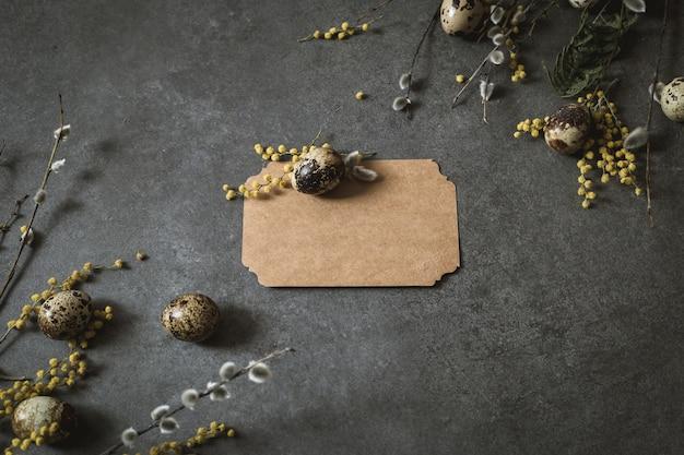 Pasen-decoratie met paaseieren en de lentebloemen. gele eieren op grijs