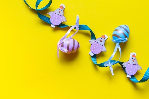 Pasen-decoratie, slinger van gekleurde eieren en houten kippenfiguren op een felgele achtergrond