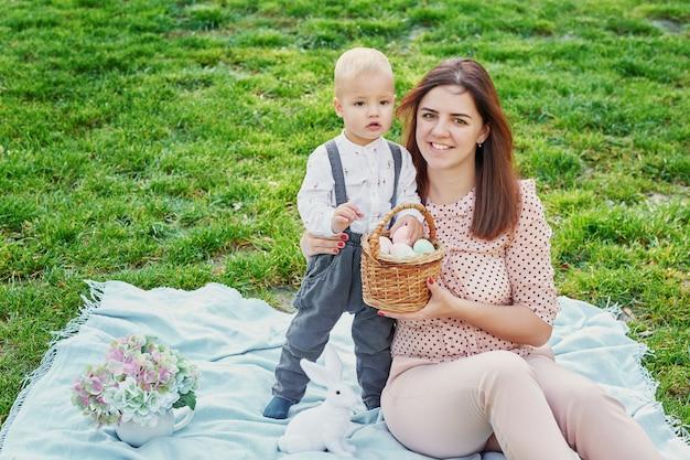 Pasen familiepicknick, oppakken van eieren, vrolijke familie op vakantie in het park. lente vakantie concept.