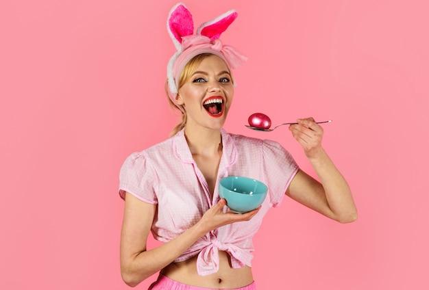 Pasen feest. vrouw met gekleurd ei. glimlachend meisje in konijntjesoren. eieren jagen.
