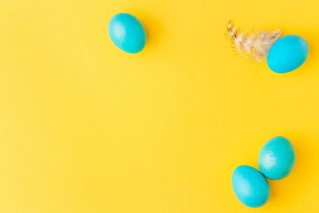 Pasen-frame dat van blauwe eieren en veer op gele achtergrond wordt gemaakt