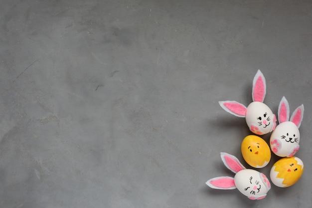 Pasen-frame, kleurrijk beschilderde eieren, konijntjes en kuikens op de grijze achtergrond. kopieer ruimte.