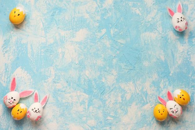 Pasen-frame, kleurrijke konijntjes en kuikens op de blauwe en witte gestructureerde achtergrond.