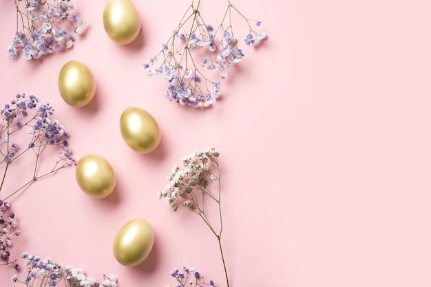 Pasen frame van gouden eieren en gipskruid op pastel roze. bovenaanzicht met kopie ruimte.