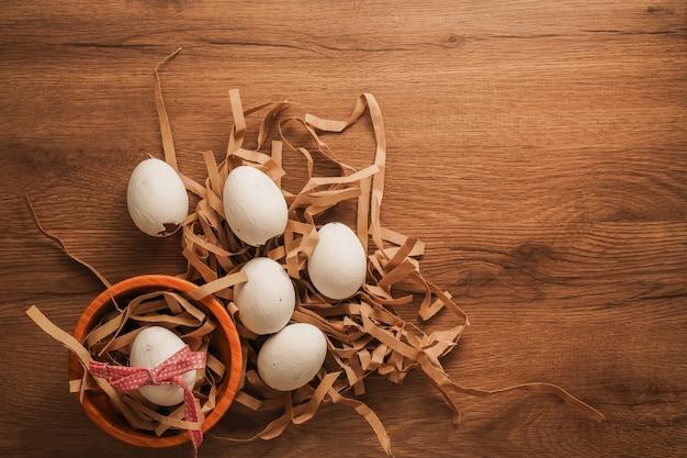 Pasen, gebonden ei met rood lint in houten kom en witte eieren op pakpapier op houten tafel