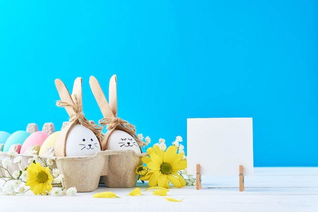 Pasen gekleurde eieren in document dienblad met decorationd op een blauwe achtergrond