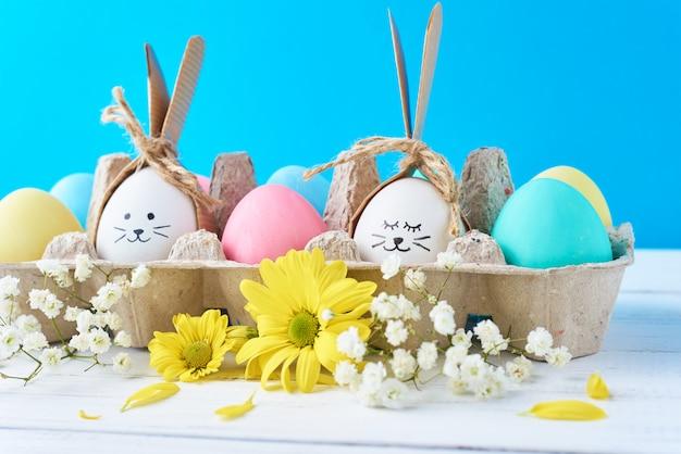 Pasen gekleurde eieren in papierlade met decorationd op een blauwe muur
