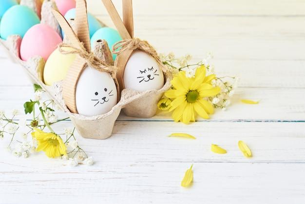 Pasen gekleurde eieren met geschilderde gezichten in document dienblad met decorationd op een witte achtergrond