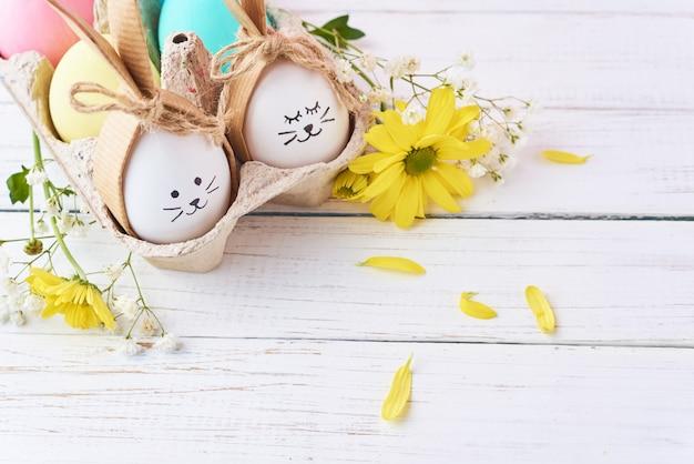 Pasen gekleurde eieren met geschilderde gezichten in papierlade met decorationd op een witte achtergrond