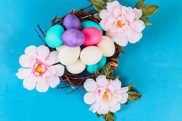 Pasen gekleurde multicolored eieren die binnen het nest naast de bloemen op een blauwe achtergrond liggen.