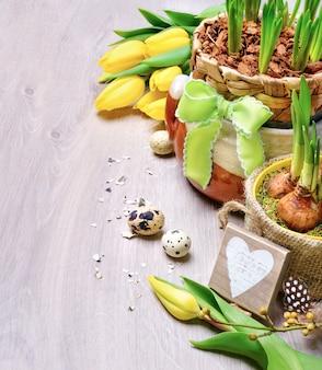 Pasen-grens met gele tulpen en natuurlijke decoratie op hout