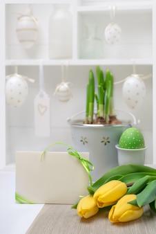Pasen-groetkaart met lint en gele tulpen