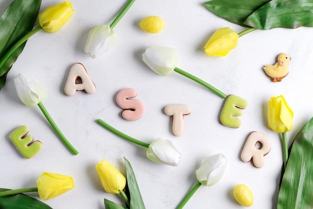 Pasen-groetkaart met tulpenbloemen, paaseieren en konijnkoekje. bovenaanzicht over witte marmeren tafel
