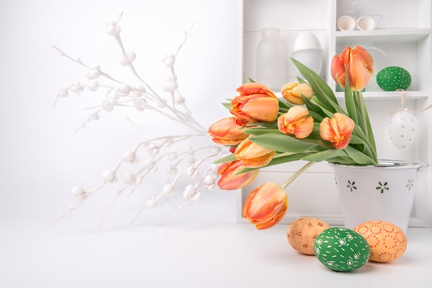 Pasen-groetontwerp met bos van tulpen en geschilderde eieren