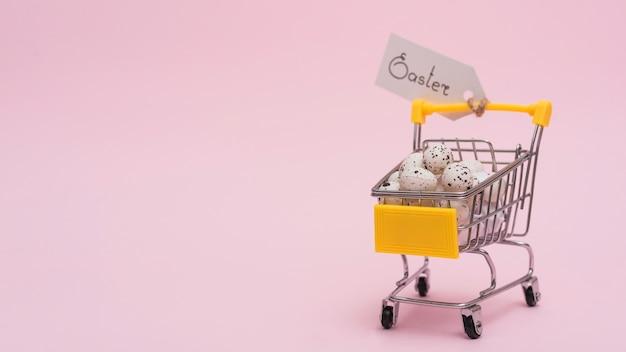 Pasen-inschrijving met eieren in kleine kruidenierswinkelkar