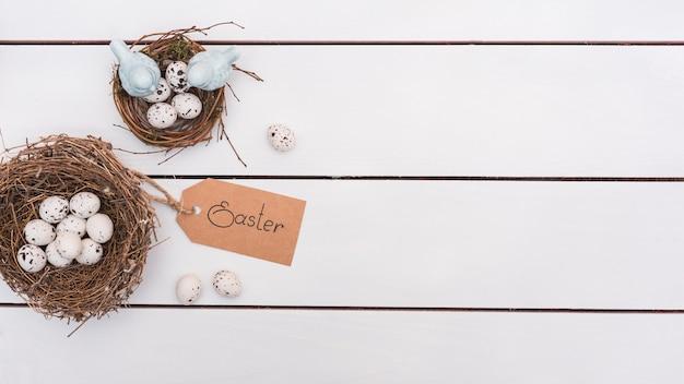 Pasen-inschrijving met kwartelseieren in nesten