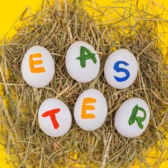 Pasen-inschrijving op witte eieren op hooi