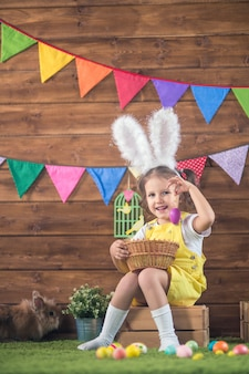 Pasen. klein meisje kind in paashaas oren met gekleurde eieren op houten achtergrond