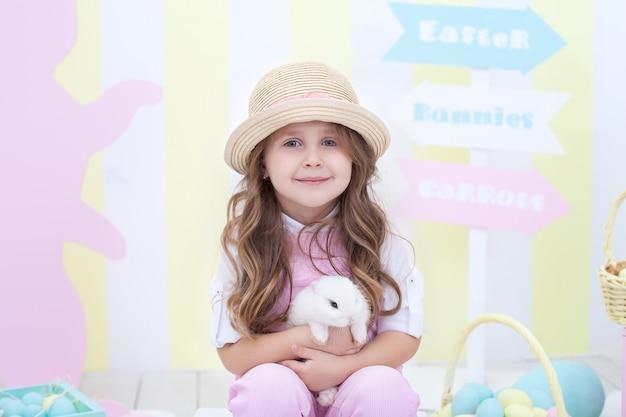 Pasen! klein meisje speelt met paashaas. een kind houdt een konijn in zijn armen op het interieur van pasen. pasen kleurrijke decor, landbouw. kind en dier. kleine boer.