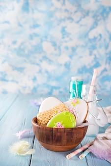 Pasen-koekjes als ei in de houten kom met melk in glas op houten achtergrond