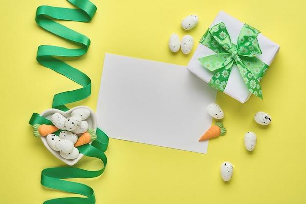 Pasen-lentegroetkaart met giftdoos met groen lint, eieren en zoete wortel op roze lijst met plaats voor tekst. bovenaanzicht.