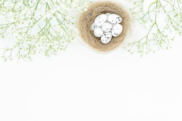 Pasen lichte achtergrond met vogelnest, eieren en kleine witte bloemen op de top