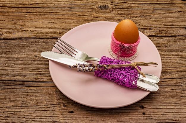Pasen-lijst die op uitstekende houten raadsachtergrond plaatsen. lente vakantie kaartsjabloon. bestek, ei, lavendel, konijntje, gebreide standaard