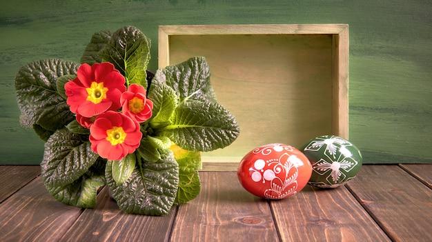Pasen-mand met geschilderde paaseieren en rode sleutelbloempotbloem op rustiek hout