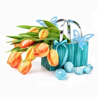 Pasen-mand met tulpen, eieren en houten vlinders op wit