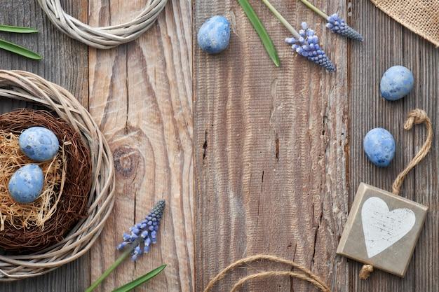 Pasen met eieren, blauwe hyacint bloemen en houten hart, bovenaanzicht op rustiek hout,