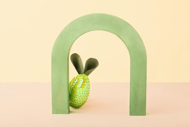 Pasen minimale conceptkaart met kopieerruimte grappig konijn van ei en oren verstopt achter een boog